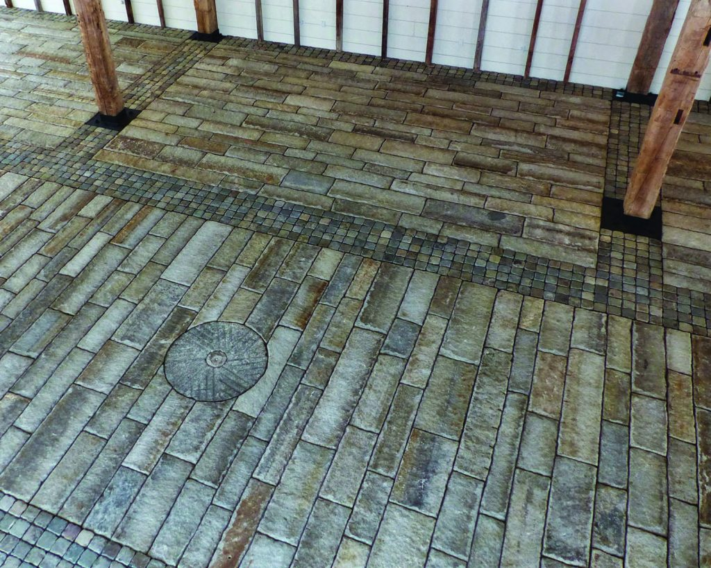 Barn floor paved with reclaimed planks and European sandstone cobblestones 4