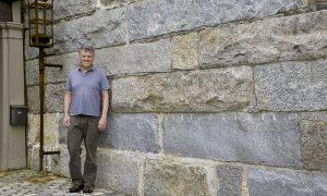 Gavin Johnston in front of reclaimed granite bridge block retaining wall